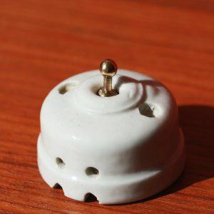 Interrupteur en porcelaine avec bouton en laiton